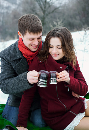 Man gently embracing a gorgeous brunette. They drink hot tea, had a picnic. Romantic feelings, love. Picturesque snow-covered Park. Fantastic shooting. Fashionable toning. Creative color.