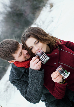 Man gently embracing a gorgeous brunette, and gives her to drink tea from their Cup.They had a picnic.Romantic feelings.Picturesque snow Park.Fantastic shooting.Fashionable toning.Creative color. Zdjęcie Seryjne