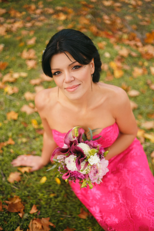 Gorgeous brunette in a luxurious slinky pink dress with bare shoulders sitting under open sky and looking at you, holding flowers.Picturesque nature.Fantastic shooting.Fashionable toning.Creative colo