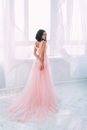 Beautiful brunette girl standing in a bright room. She is dressed in luxurious, fluffy, pink dress. Gentle puppets face. The European image of the bride. Photo high key style. 写真素材