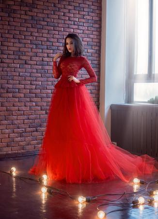 Schönes Brunettemädchen, das im Raum steht. Sie ist in einem luxuriösen, üppigen, roten Kleid gekleidet. Frau mit sanftem Puppengesicht