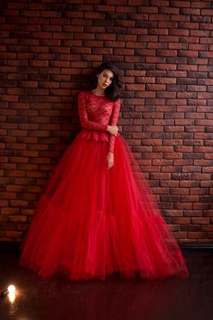 Schönes Brunettemädchen, das im Raum steht. Sie ist in einem luxuriösen, üppigen, roten Kleid gekleidet. Frau mit sanftem Puppengesicht Standard-Bild