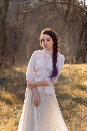 Beautiful brunette girl standing on the meadow. She is dressed in luxurious, beige, vintage dress. The European image of the bride 写真素材