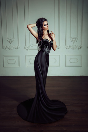 Beautiful brunette girl in a luxurious, black dress. Indian woman in the role of a chess piece. Black queen. 写真素材