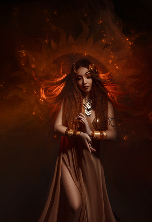 Beautiful, red-haired girl - a priestess of the sun. Dress and jewelry in ethnic style. Unusual make-up in orange and gold tones. Fantastic photography, fashionable toning.