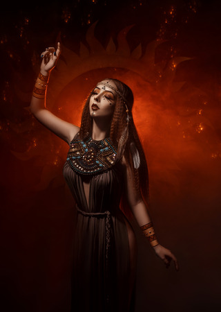 Beautiful, red-haired girl - a priestess of the sun. Dress and jewelry in ethnic style. Unusual make-up in orange and gold tones. Girl praying in silence.  Fantastic photography, fashionable toning.