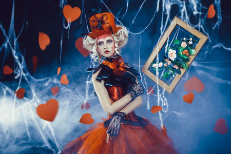 Queen of Hearts entered into the real world. Photo shoot in the style of the card game. Unusual, creative make-up, beautiful, funny dress. Vintage hairstyle. Studio photography, fashionable toning Stock Photo
