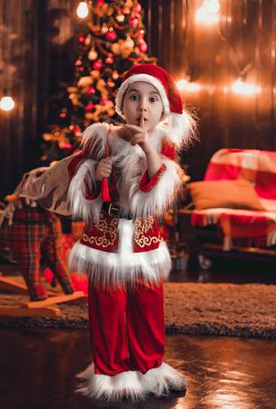 sneaks: Little Santa sneaks into the house. Christmas funny story. The festive mood. Creative colors.