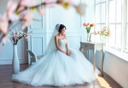 Beautiful young girl sitting on banquette in a bright room.She is dressed in luxurious, fluffy, white dress.She looking Flirty down.European image of bride.Fashionable toning.Creative color.