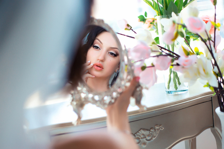 Beautiful young brunette in a bright room.She looking Flirty in mirror,reflection.European image of bride.Photo high key style.Fashionable toning.Creative color. Stockfoto