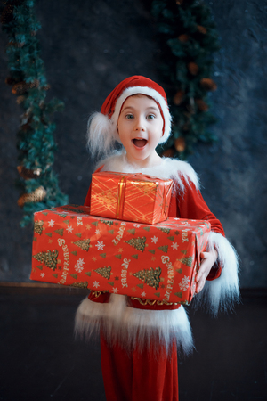 Little Santa brings gifts. Christmas funny story. The festive mood. Creative colors. Stock Photo