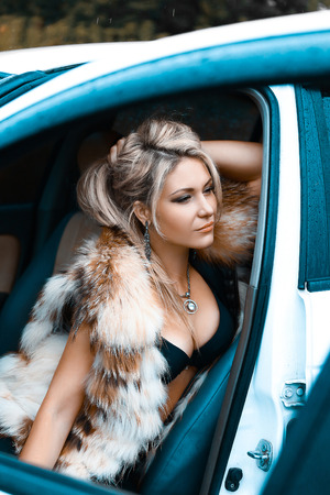 Beautiful sexy young girl sitting in a car with an open door,she dressed in a royal fur vest.Long chic curls, languid dreamy look to side.Photos in style of high key.Fashionable toning.Creative color. Stock Photo