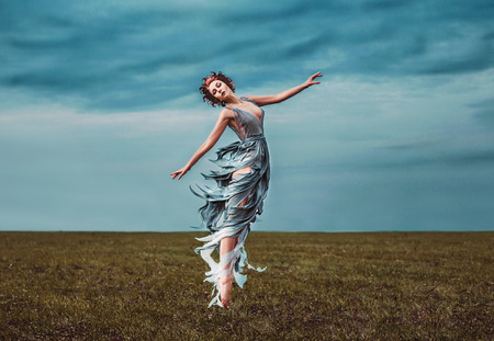 Girl muse, dancing in a field. As the picture from an old book. Fashionable toning, picture in the style of fantasy. Background gloomy, cold, stormy, autumn sky. 版權商用圖片 - 70718283