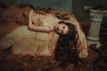 Tale of Sleeping Beauty. The girl is in the old, abandoned room. It covered the dust and leaves. Autumn atmosphere of sadness. Beautiful, long, wavy hair.  Princess lying on the bed and looking at the camera.  Creative colors Banque d'images