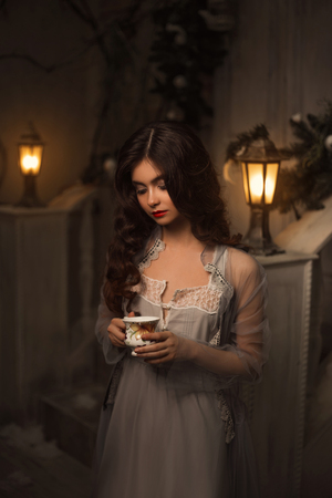The Winter's Tale. Beautiful woman in vintage dress standing next to the house with a cup of tea. Long hair, baby face. Creative colors Stockfoto