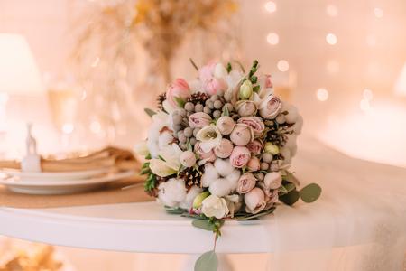 Mooie boeketbruid in de winterstijl. Ongebruikelijke bloemenregeling, pastelkleuren. Universele inrichting, feeststemming.
