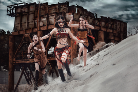 Warrior. Wild american indian girl ran to attack its prey. Ethnic shot against the background of an old rusty structure and sand. Unusual savage costume, jewelry, makeup combat. Fashionable toning. Stockfoto