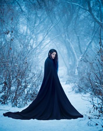 Het meisje een demon loopt alleen. Ze draagt een lange zwarte mantel reizen. Stockfoto