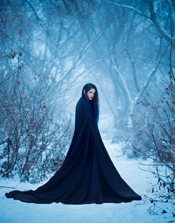 The girl a demon walks alone. She is wearing a long, black traveling cloak. Stock Photo