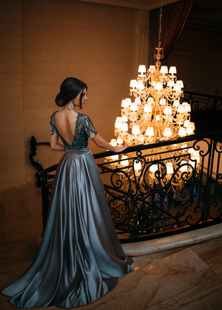 Girl in a luxurious, evening dress standing on the stairs. Creative colors Foto de archivo