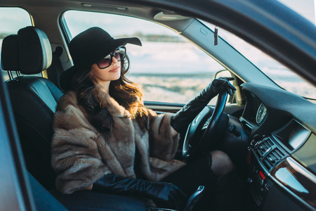 Young beautiful brunette inside the car with wheel in hands Stockfoto