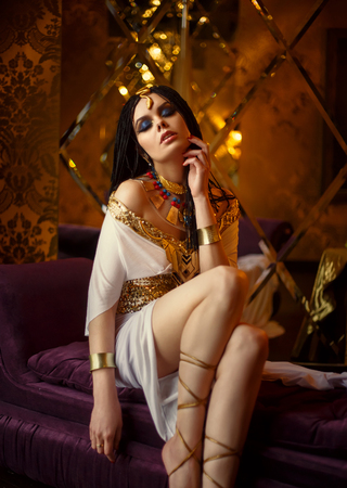 Junge Königin in den reichen Kammern. Das Mädchen ist in einem griechischen Kleid und Goldschmuck mit Schlangen und Skarabäen gekleidet. Standard-Bild - 74339907