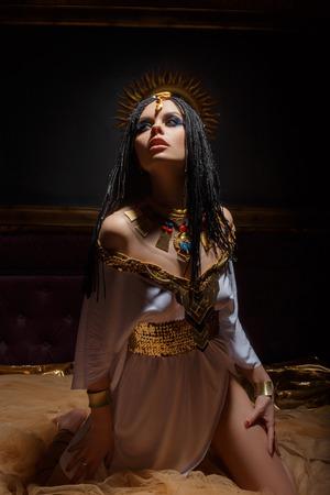 Jeune reine dans les chambres riches. La jeune fille est vêtue d'une robe grecque et des bijoux en or avec des serpents et des scarabées. Banque d'images - 74010133