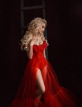 Blonde girl in a luxurious dress with a long train. Gold make-up. Creative colors