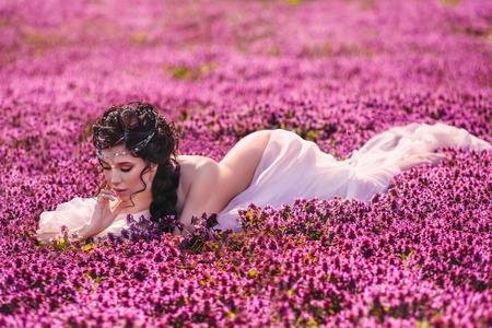 Ein schönes Mädchen in einem weißen Vintage-Kleid. Lange Haare sind eng geflochten. Die griechische Göttin ruht in einem Feld von Blumen. Standard-Bild - 77819981