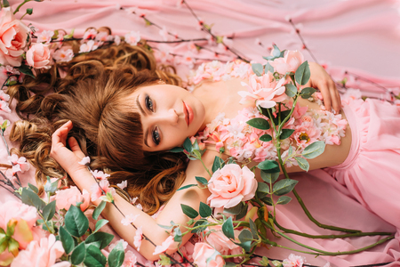 Young woman and many flowers. Princess in a pink dress. Creative colors