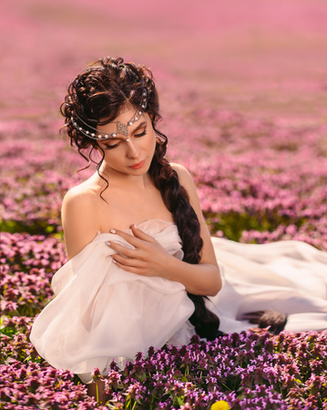 Une belle fille vêtue d'une robe vintage blanche. Les cheveux longs sont étroitement tressés. La déesse grecque se repose dans un champ de fleurs. Banque d'images - 78432370