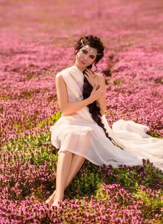 Ein schönes Mädchen in einem weißen Vintage-Kleid. Lange Haare sind eng geflochten. Die griechische Göttin ruht in einem Feld von Blumen. Standard-Bild - 78432405