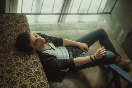 appearance: A young guy smokes at the entrance. Beautiful appearance, clothes in rock style. Creative colors