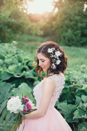 Beautiful girl bride with a bouquet. She wears a beautiful pink dress, her hair is decorated with flowers. Creative colors