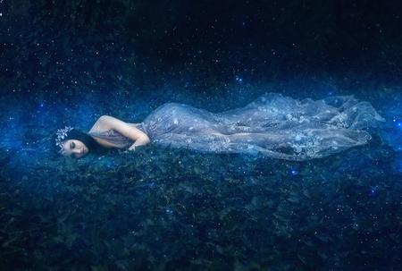 Mooi jong meisje slaapt in de armen van de ruimte onder de sterren, fantasiefotoshoot, modieuze toning, creatieve kleur Stockfoto