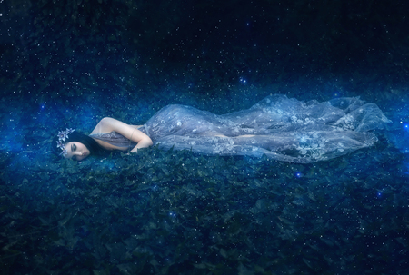 Beautiful young girl sleeps in the arms of space among the stars , fantasy fotoshoot , fashionable toning , creative color