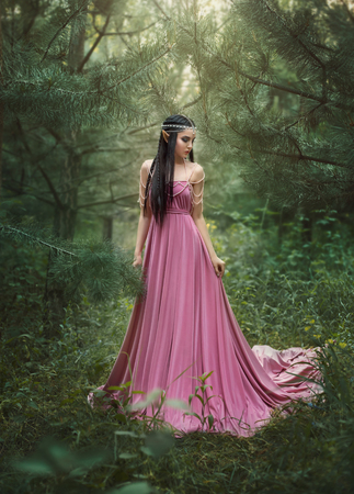 The elf walks in the garden. A girl with long ears in a beautiful pink dress with an open back and with a long train. Artistic processing
