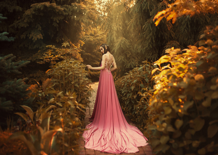 The Elf walks in the autumn garden. A girl with long ears in a beautiful pink dress with an open back and with a long train. Artistic processing