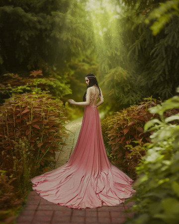 The elf walks in the summer garden. A girl with long ears in a beautiful pink dress with an open back and with a long train. Artistic processing