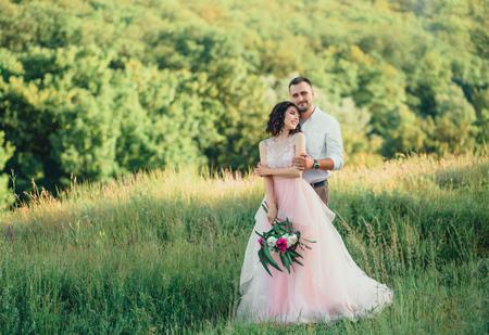 Mooie bruiloft in de natuur. Jurk in Boho stijl. Kapsel voor kort haar met bloemen. Een geliefde paar loopt bij zonsondergang.