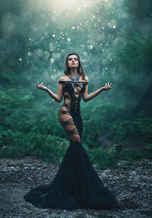 A beautiful girl in an unusual black, sexy dress strolls in the forest. Wild Princess , vampire, creative color, dark boho