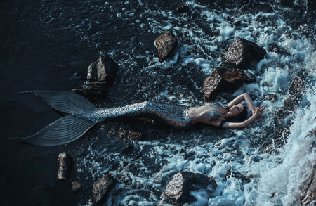 The real mermaid is resting on the ocean shore. Silver tail, the body is covered with scales. Creative colors 写真素材