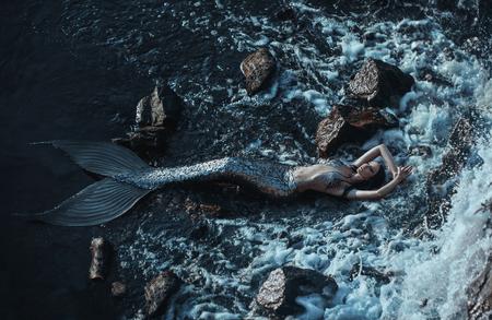 진짜 인어가 바다 기슭에 휴식 중입니다. 실버 테일, 몸은 비늘로 덮여 있습니다. 창조적 인 색상 스톡 콘텐츠