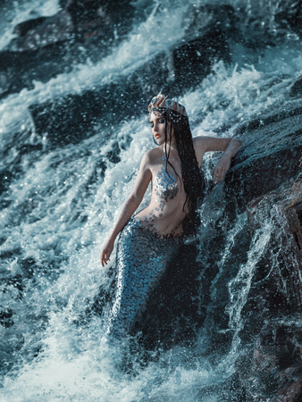 The real mermaid is resting on the ocean shore. Silver tail, the body is covered with scales. Creative colors Banque d'images