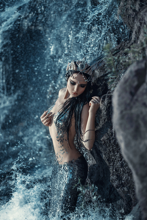 The real mermaid is resting on the ocean shore. Silver tail, the body is covered with scales. Creative colors Standard-Bild
