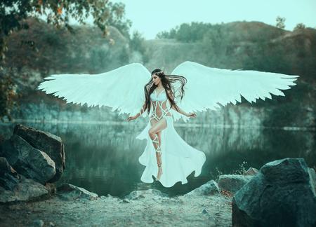 Ein schöner weißer Erzengel stieg vom Himmel herab. Ein Mädchen in einem sexy Anzug mit riesigen weißen Flügeln. Künstlerische Fotografie
