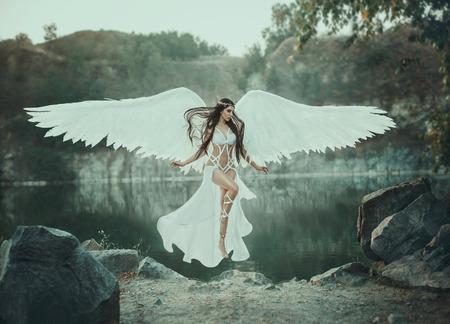 Ein schöner weißer Erzengel stieg vom Himmel herab. Ein Mädchen in einem sexy Anzug mit riesigen weißen Flügeln. Künstlerische Fotografie Standard-Bild