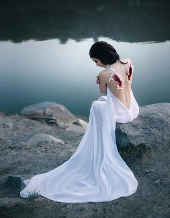 Un ángel caído con las alas arrancadas. La niña se arrepiente de sus pecados, las heridas en su espalda, las marcas de sus alas. Fotografía artística