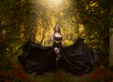 The dark queen of elves walks in the magical garden. A creative image, an unusual black dress. Artistic toning. Stock Photo
