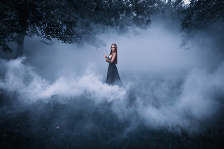 The dark queen of elves walks in a misty forest. A creative image, an unusual black dress. Artistic toning.